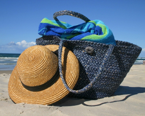 Beach bag essentials include hat, sunscreen, coverup, books and music