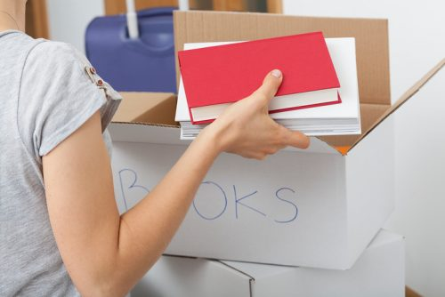 Girl arranging different types of books in descripted boxes